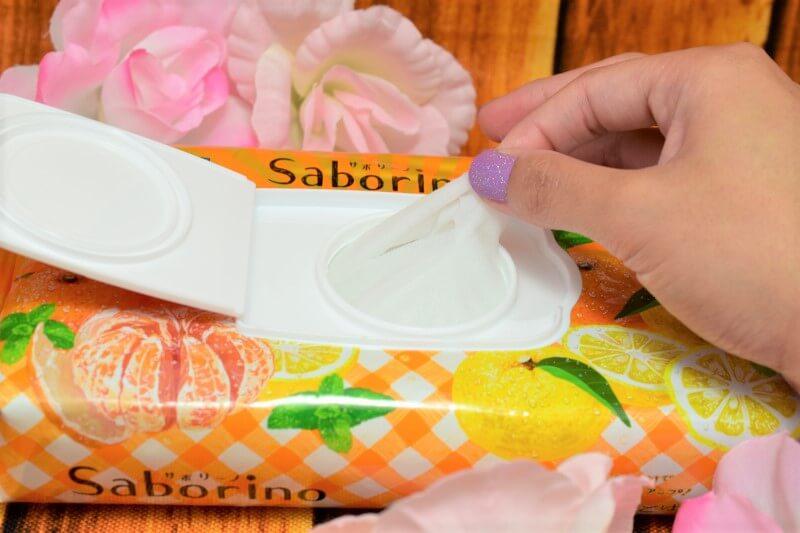 サボリーノ 目ざまシート 贅沢果実の濃密タイプ(ゆずシトラスの香り)のパッケージからマスクを取り出している様子